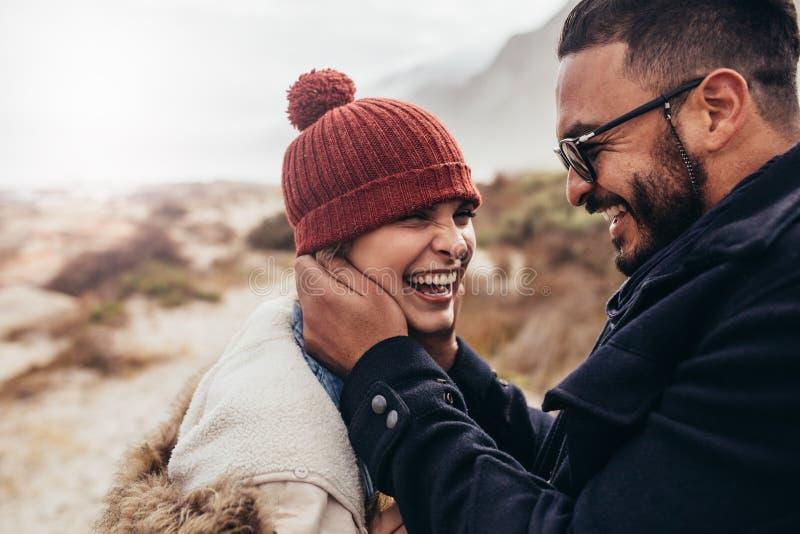 Glimlachend paar die van een de winterdag genieten bij het strand royalty-vrije stock afbeeldingen