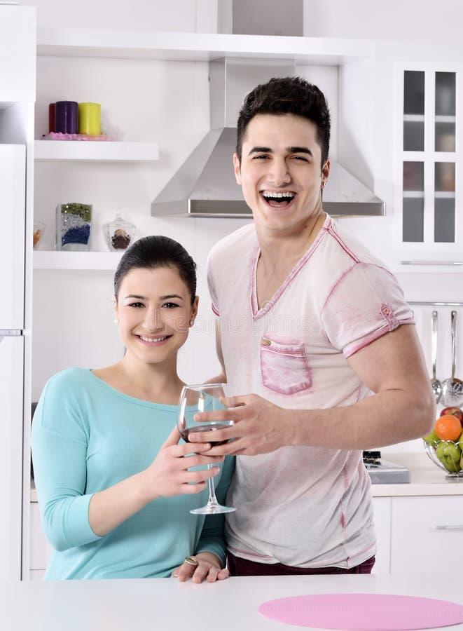 Glimlachend paar die van rode wijnstok in de keuken genieten royalty-vrije stock fotografie