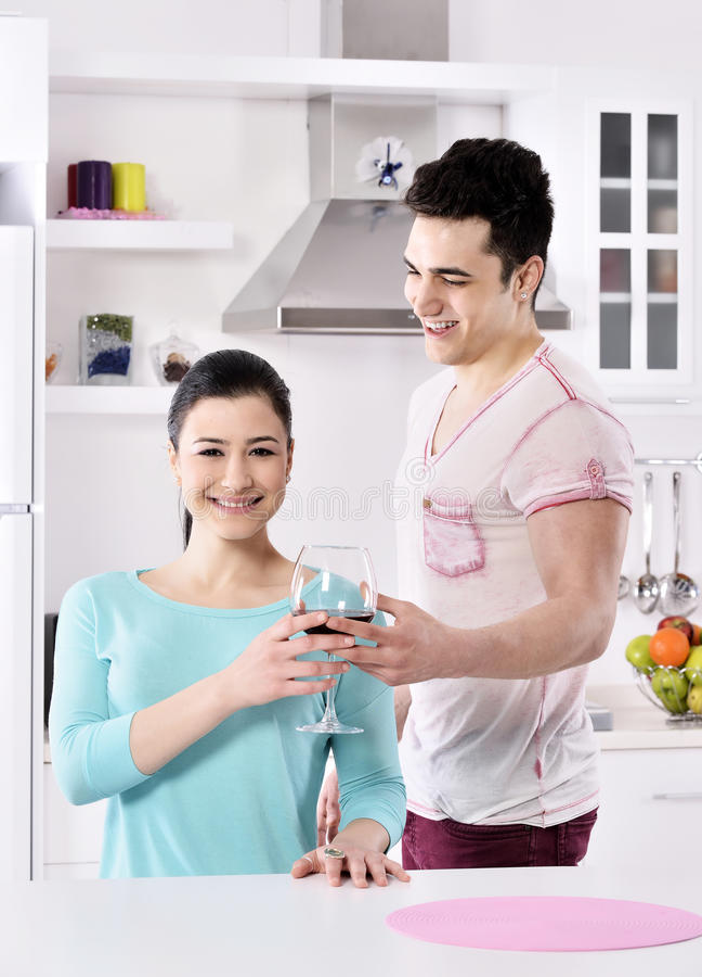 Glimlachend paar die van rode wijnstok in de keuken genieten stock foto's