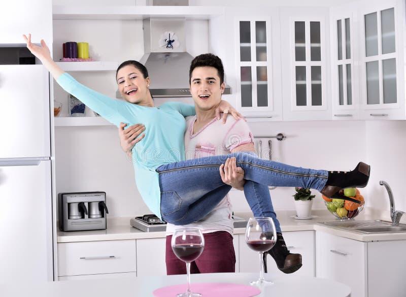 Glimlachend paar die van rode wijnstok in de keuken genieten stock foto