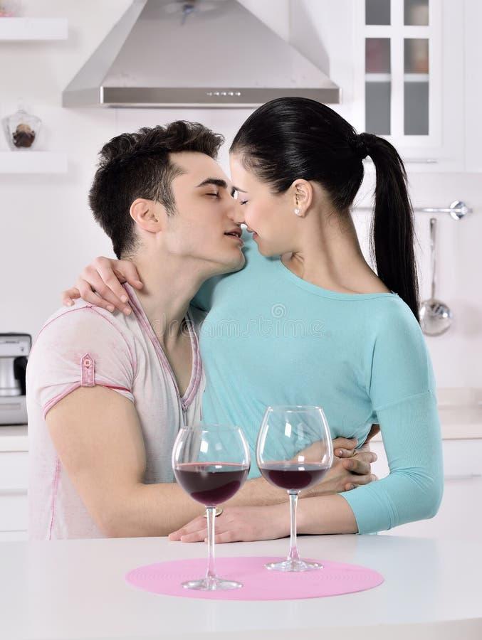 Glimlachend paar die van rode wijnstok in de keuken genieten stock afbeelding