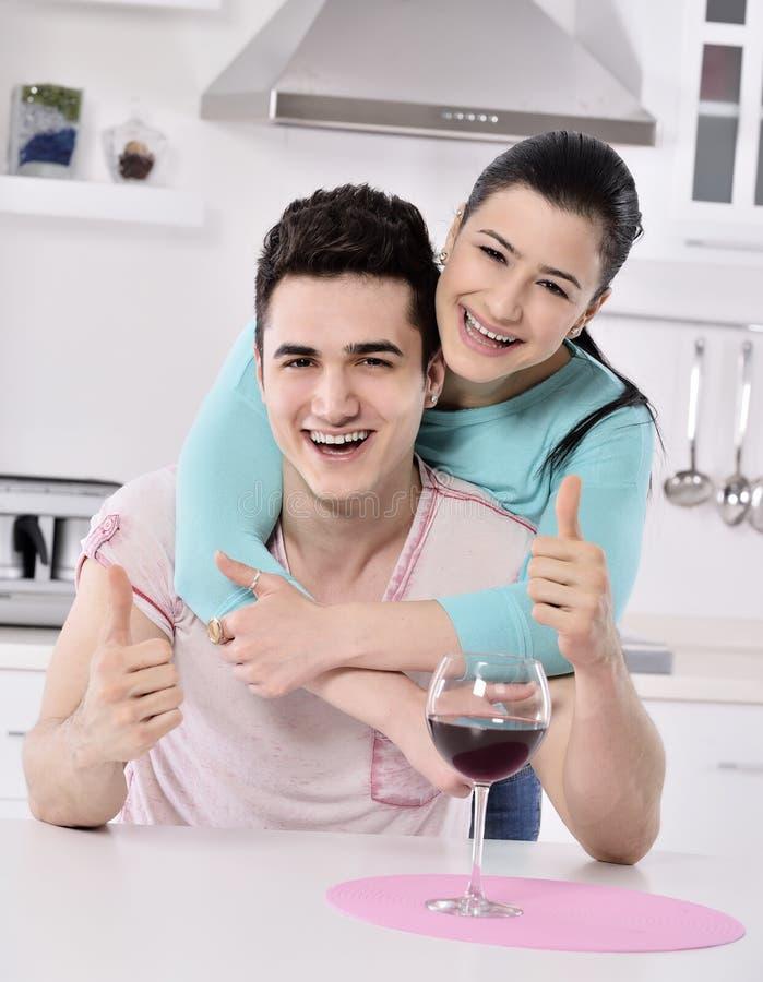 Glimlachend paar die van rode wijnstok in de keuken genieten royalty-vrije stock foto's