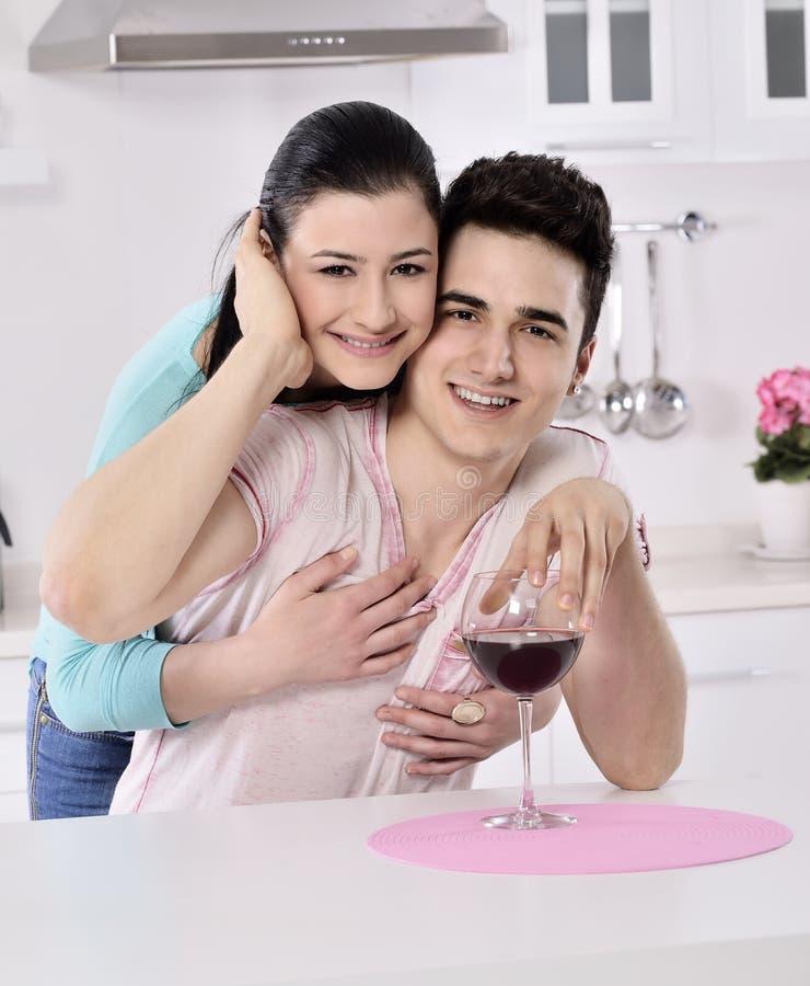 Glimlachend paar die van rode wijnstok in de keuken genieten royalty-vrije stock afbeeldingen
