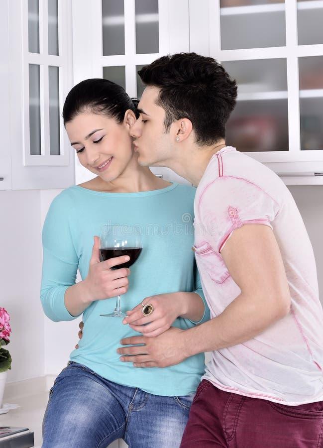 Glimlachend paar die van rode wijnstok in de keuken genieten stock afbeeldingen