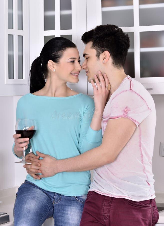 Glimlachend paar die van rode wijnstok in de keuken genieten royalty-vrije stock afbeelding