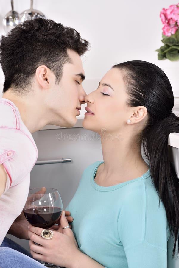 Glimlachend paar die van rode wijnstok in de keuken genieten royalty-vrije stock foto