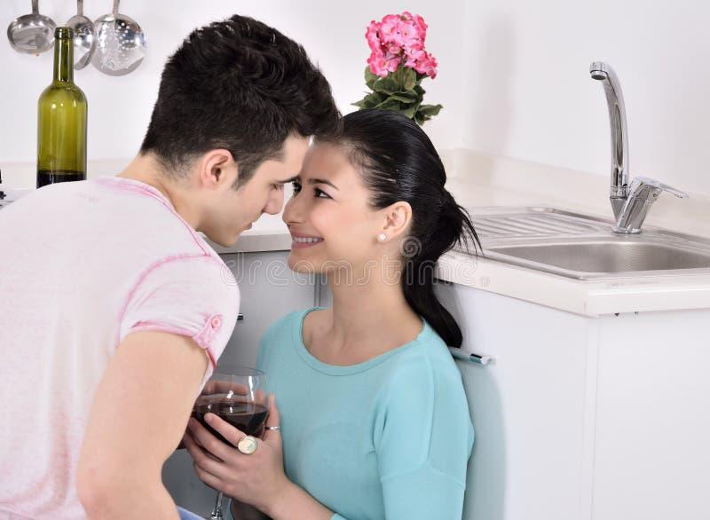 Glimlachend paar die van rode wijnstok in de keuken genieten stock fotografie