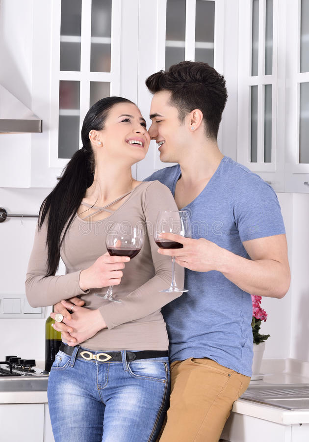 Glimlachend paar die van rode wijnstok in kitchev genieten royalty-vrije stock foto's