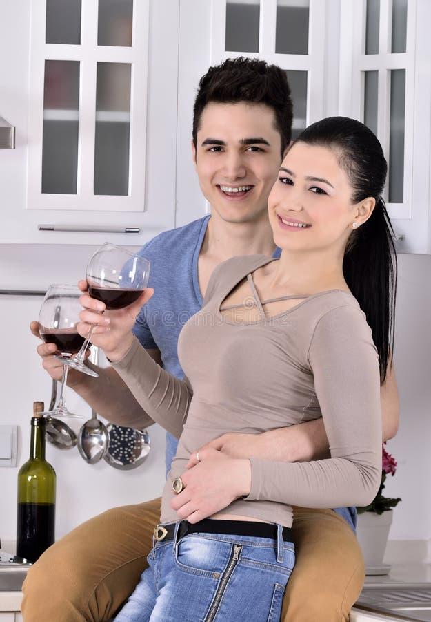 Glimlachend paar die van rode wijnstok in kitchev genieten stock fotografie