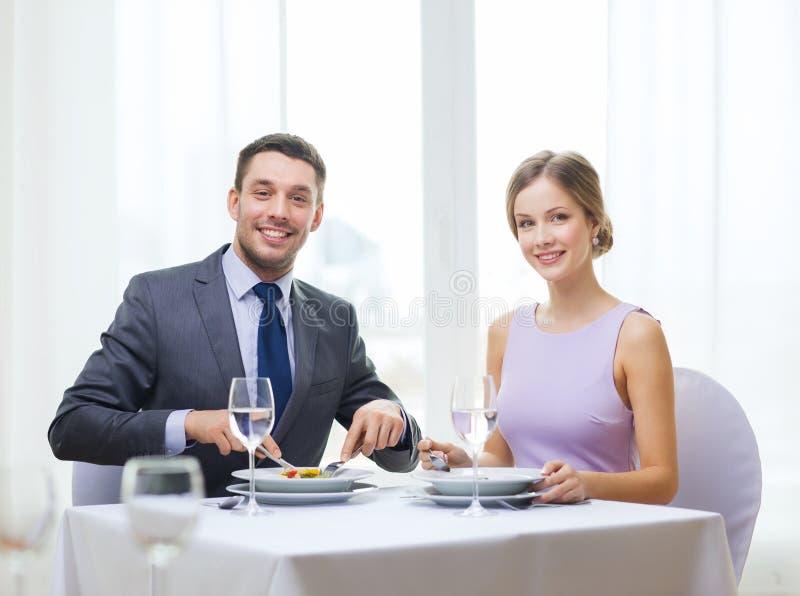 Glimlachend paar die voorgerechten eten bij restaurant royalty-vrije stock afbeeldingen