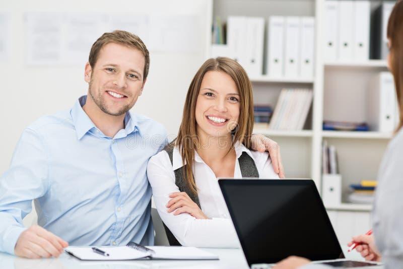 Glimlachend paar in een vergadering met een adviseur royalty-vrije stock afbeelding