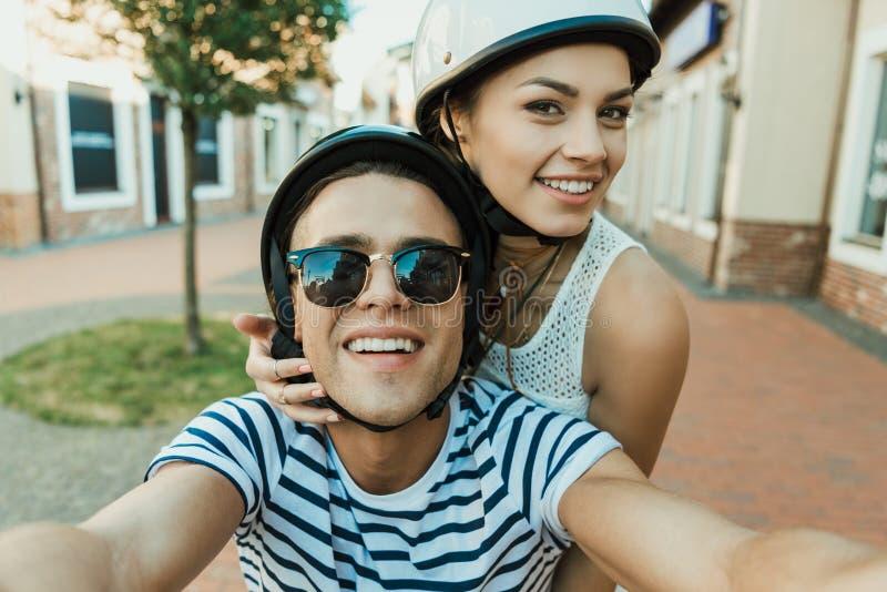 Glimlachend paar in helmen die selfie in openlucht nemen stock foto