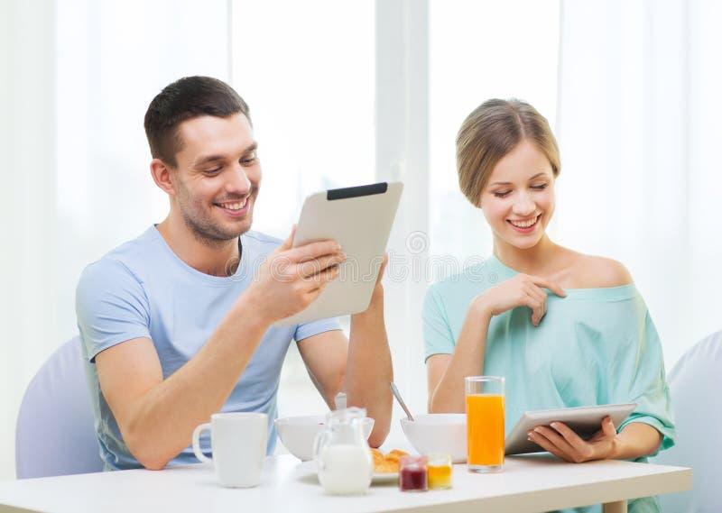 Glimlachend paar met de lezingsnieuws van tabletpc stock afbeelding