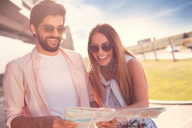 Glimlachend paar met een kaart royalty-vrije stock foto