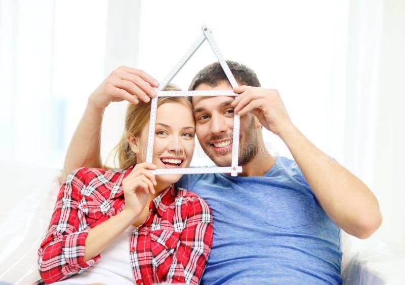 Glimlachend paar met huis van het meten van band royalty-vrije stock foto