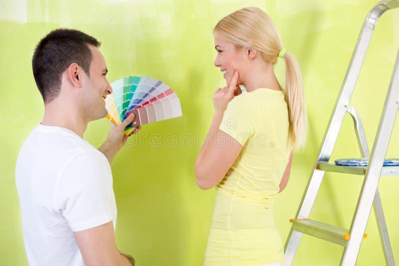 Glimlachend paar met kleurensteekproeven aan verf royalty-vrije stock afbeeldingen