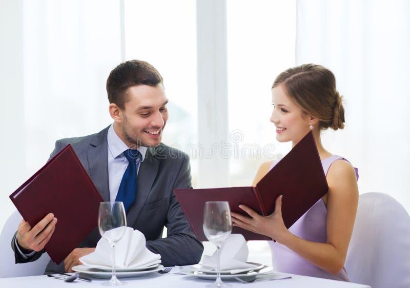 Glimlachend paar met menu's bij restaurant stock foto's
