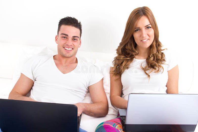 Glimlachend paar met twee laptop computers in bed stock foto's