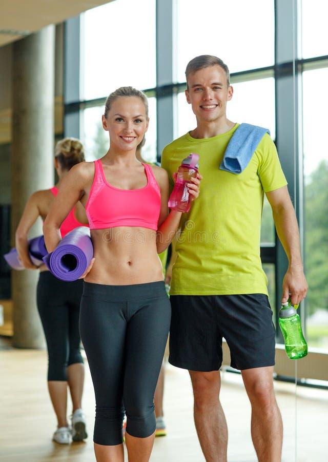 Glimlachend paar met waterflessen in gymnastiek stock foto's