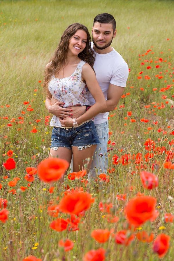 Glimlachend paar in papaversinstallaties stock afbeelding