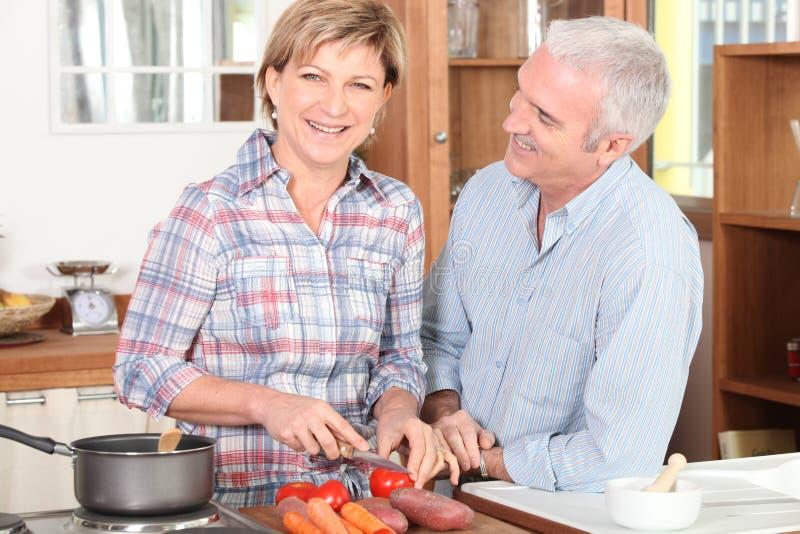 Glimlachend paar van oudste in keuken stock foto