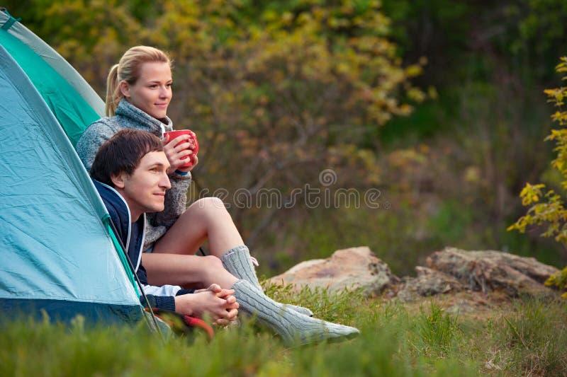 Glimlachend paar van toeristen met kop thee die dichtbij de tent spreken royalty-vrije stock foto's