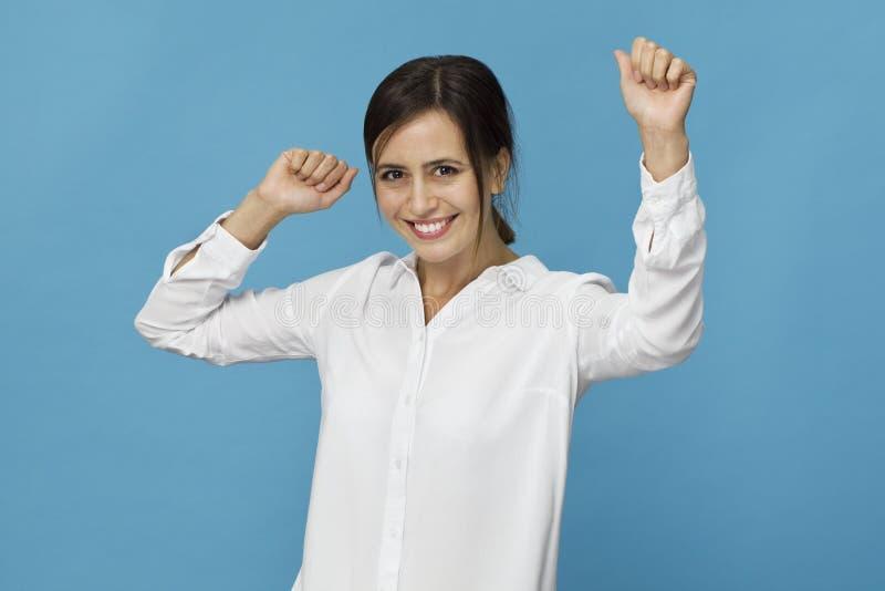 Glimlachend positief wijfje die met aantrekkelijke blik, witte T-shirt dragen, die tegen blauwe blinde muur stellen stock afbeelding