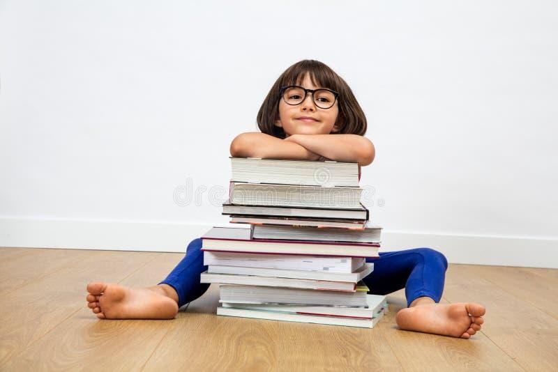 Glimlachend primair kind met oogglazen die op stapel van boeken leunen royalty-vrije stock foto's