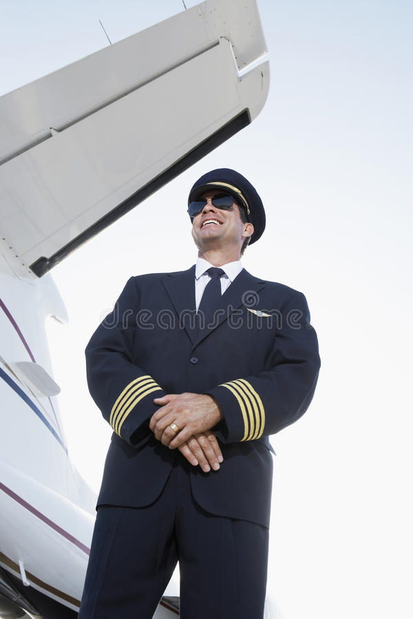Glimlachend Proefin uniform beside een Vliegtuig stock afbeelding
