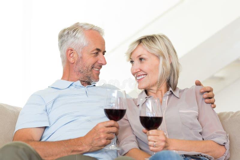 Glimlachend rijp paar die met wijnglazen op bank zitten royalty-vrije stock foto