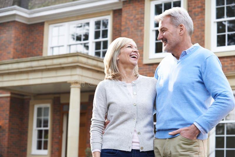 Glimlachend Rijp Paar die zich buiten Huis bevinden stock afbeeldingen