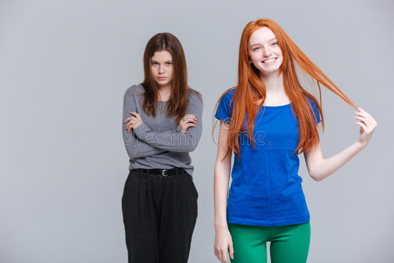 Glimlachend roodharige twee en verstoorde donkerbruine jonge vrouwen stock afbeelding