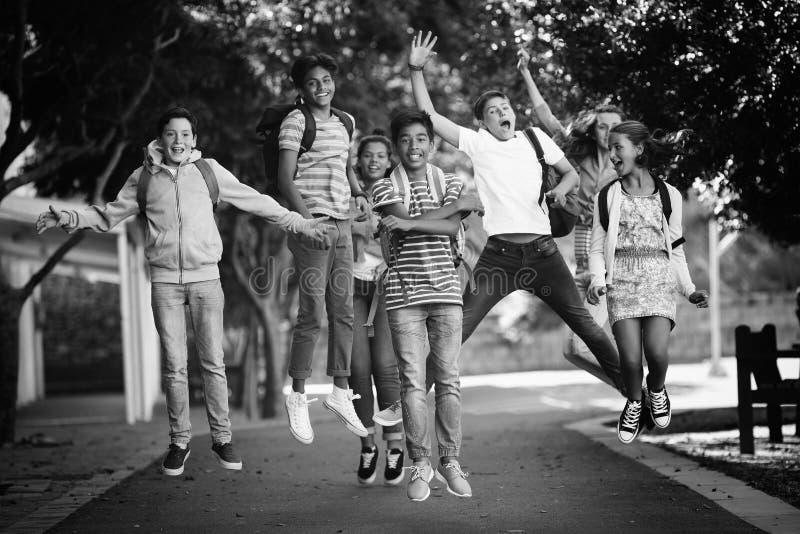 Glimlachend schooljonge geitjes die pret op weg in campus hebben royalty-vrije stock afbeelding