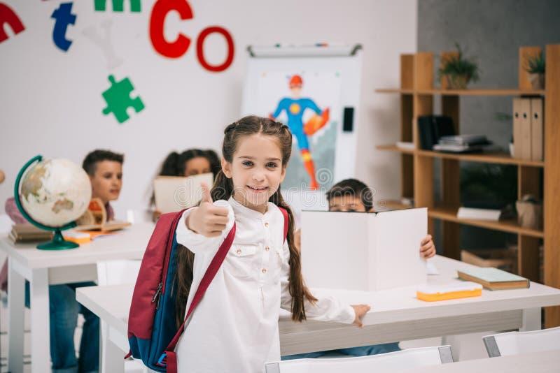 Glimlachend schoolmeisje die duim tonen terwijl klasgenoten die erachter bestuderen royalty-vrije stock afbeeldingen