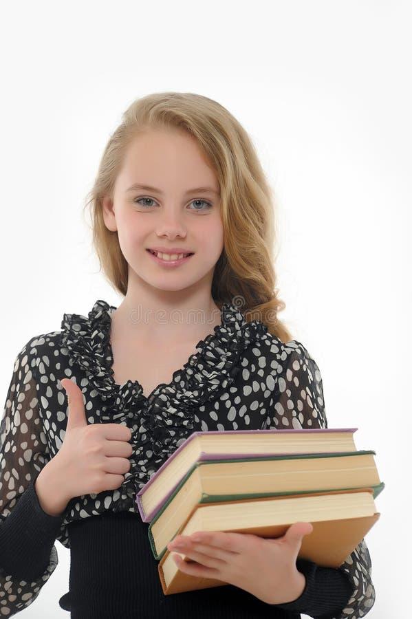 Glimlachend schoolmeisje met boeken stock foto