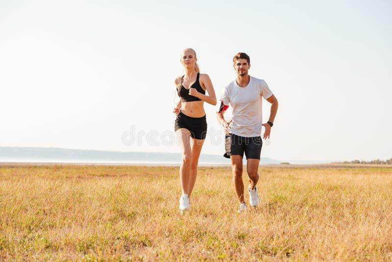 Glimlachend sportenpaar die in openlucht lopen stock fotografie