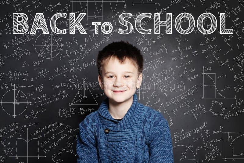 Glimlachend Studentenkind die op bord met wiskundeformules denken stock afbeeldingen