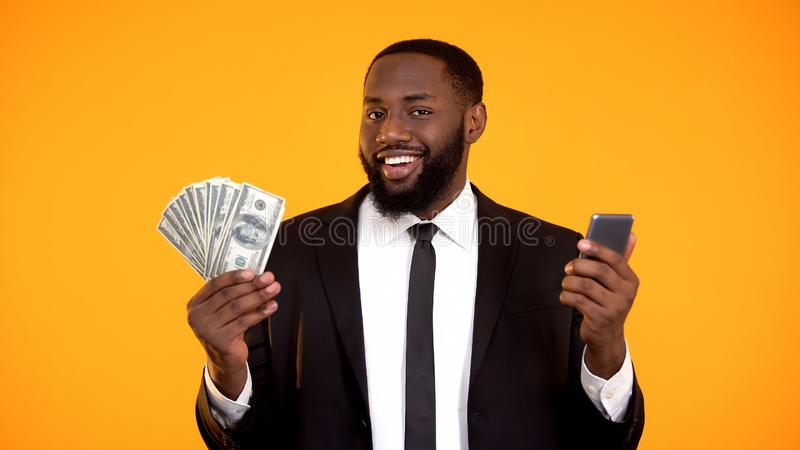 Glimlachend Succesvol zwart mannetje in de telefoon en de dollarrekeningen van de kostuumholding, cashback royalty-vrije stock foto
