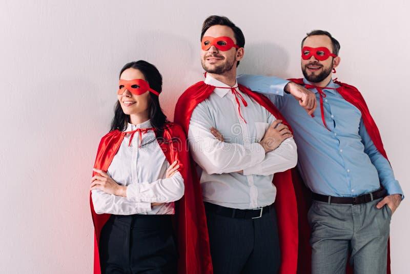 glimlachend super zakenlui in maskers en kaap die weg eruit zien stock afbeelding