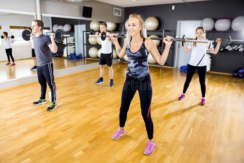 Glimlachend team die hurkende oefeningen met gewichten doen bij geschiktheidsgymnastiek stock foto