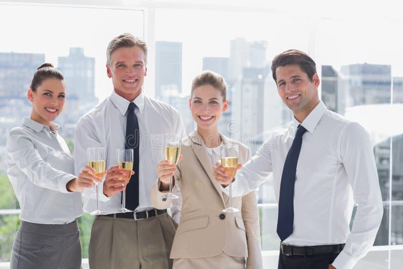 Glimlachend team van bedrijfsmensen die een succes met champagn eren stock fotografie