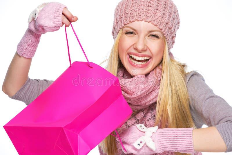 Glimlachend tienermeisje in de winterhoed en sjaal het openen het winkelen zak stock foto's