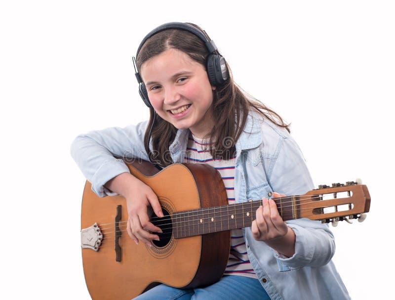 Glimlachend tienermeisje die akoestische gitaar op wit spelen stock foto