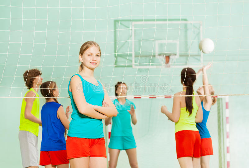 Glimlachend tienermeisje die zich naast netto volleyball bevinden royalty-vrije stock foto's