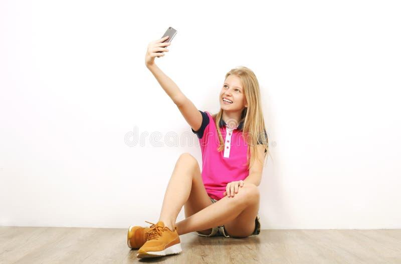 Glimlachend tienermeisje in het toevallige uitrusting stellen met mobiele telefoon, die emoties tonen, die grappige gezichten mak stock afbeeldingen