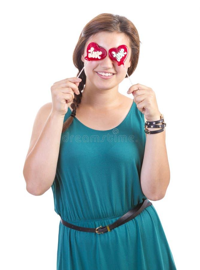 Glimlachend tienermeisje met hart gevormde lolly royalty-vrije stock afbeelding