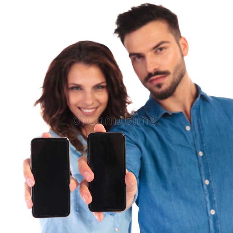 Glimlachend toevallig paar die de lege schermen van hun telefoons tonen royalty-vrije stock foto