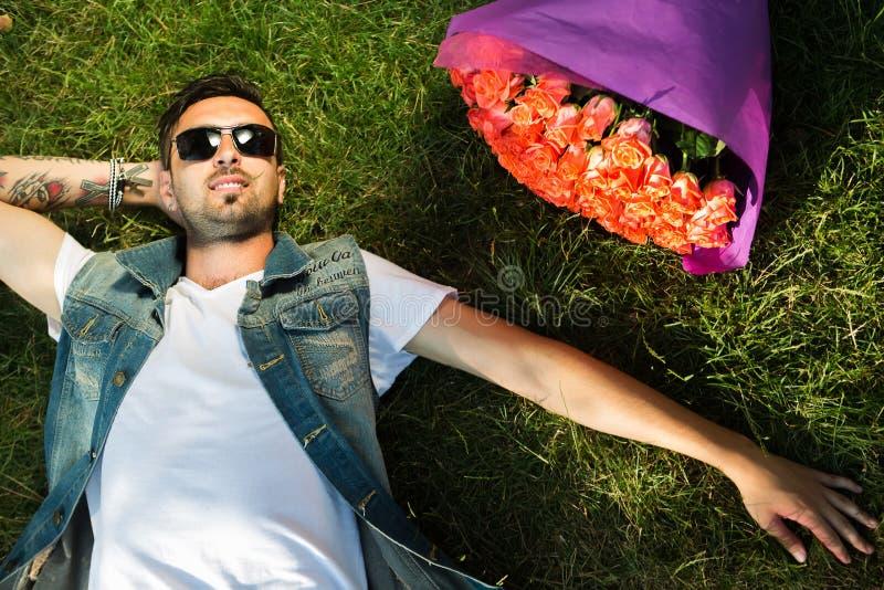 Glimlachend valentijnskaartmannetje met bos van rozen die op gras liggen stock fotografie