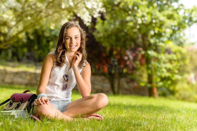 Glimlachend van het de zittingsgras van het studentenmeisje de zomerpark royalty-vrije stock afbeelding