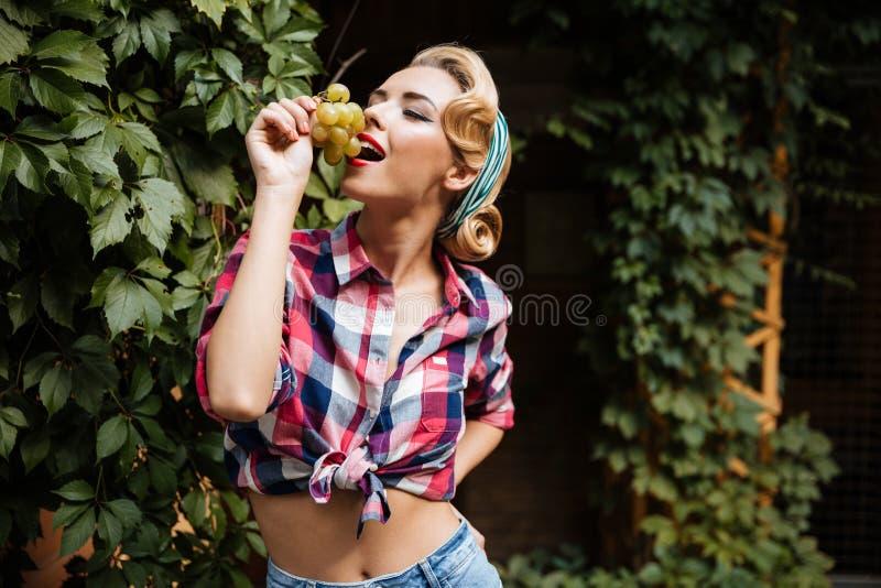 Glimlachend verleidelijk pinupmeisje die druif in de tuin eten stock afbeelding